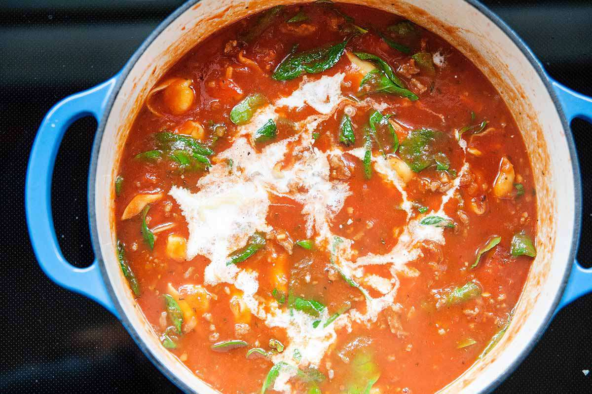 Tomato Basil Tortellini Soup - shot of tortellini soup in pot with spinach with cream