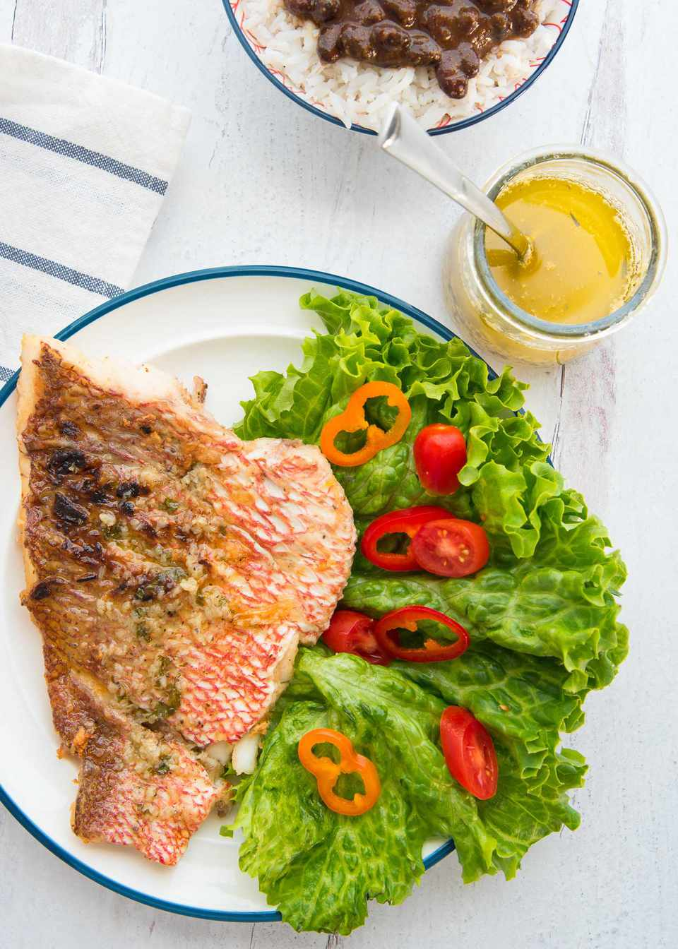 Red snapper with garlic sauce is on a white plate with a blue stripe around the edge. The snapper is crispy and takes up half of the plate. A green leafy salad with red and orange peppers is on the other side of the plate. A jar of garlic sauce is to the upper right of the salad. A bowl of rice and beans with cilantro is to the upper left of the jar of sauce. A striped napkin are to the left of the snapper.