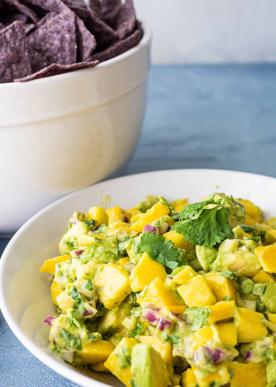 Salsa with Mangos and Avocado - - bowl of mangos and avocadoswtih chips in the bacground