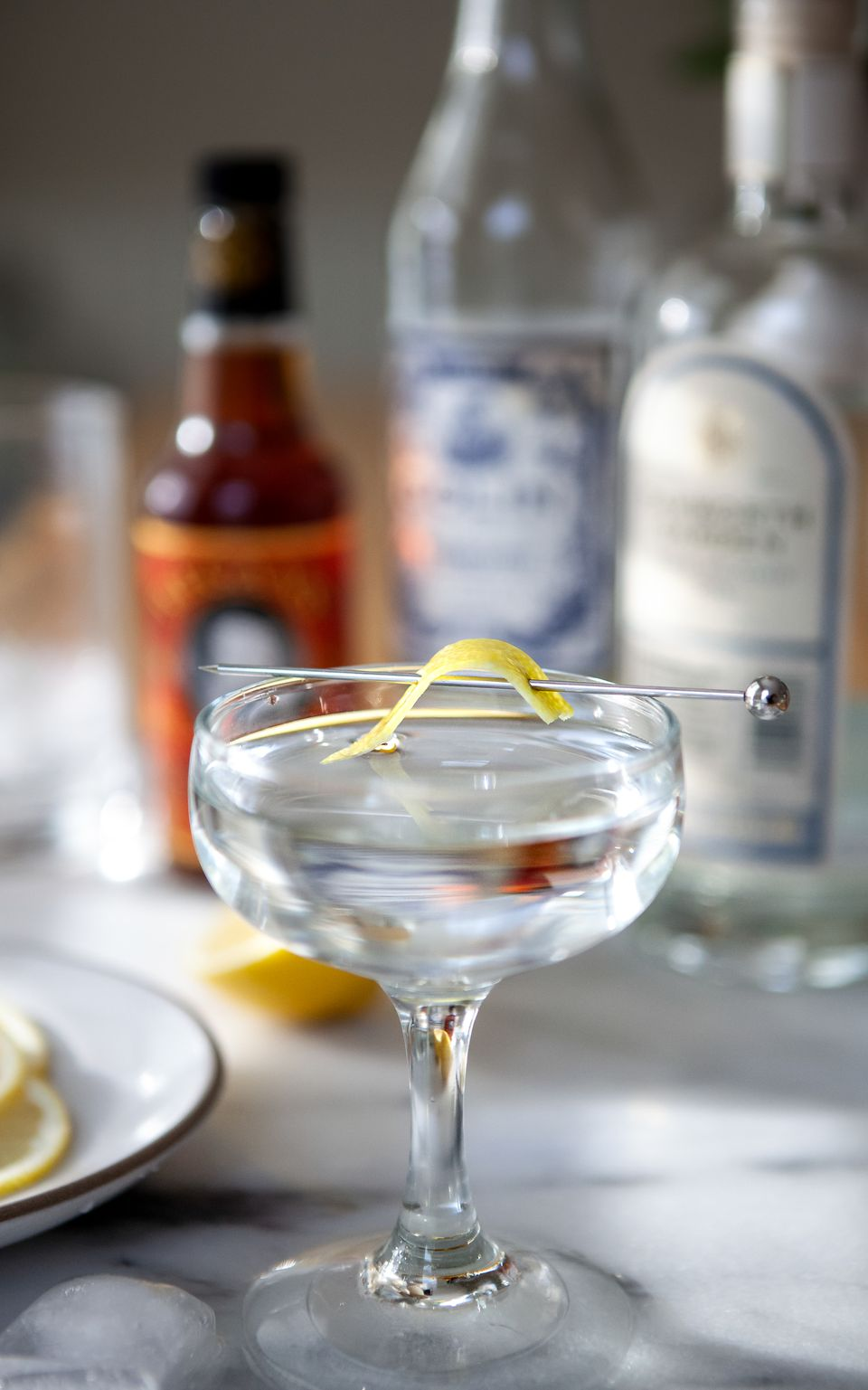 Classic Gin Martini in a coupe with bottles set behind it.