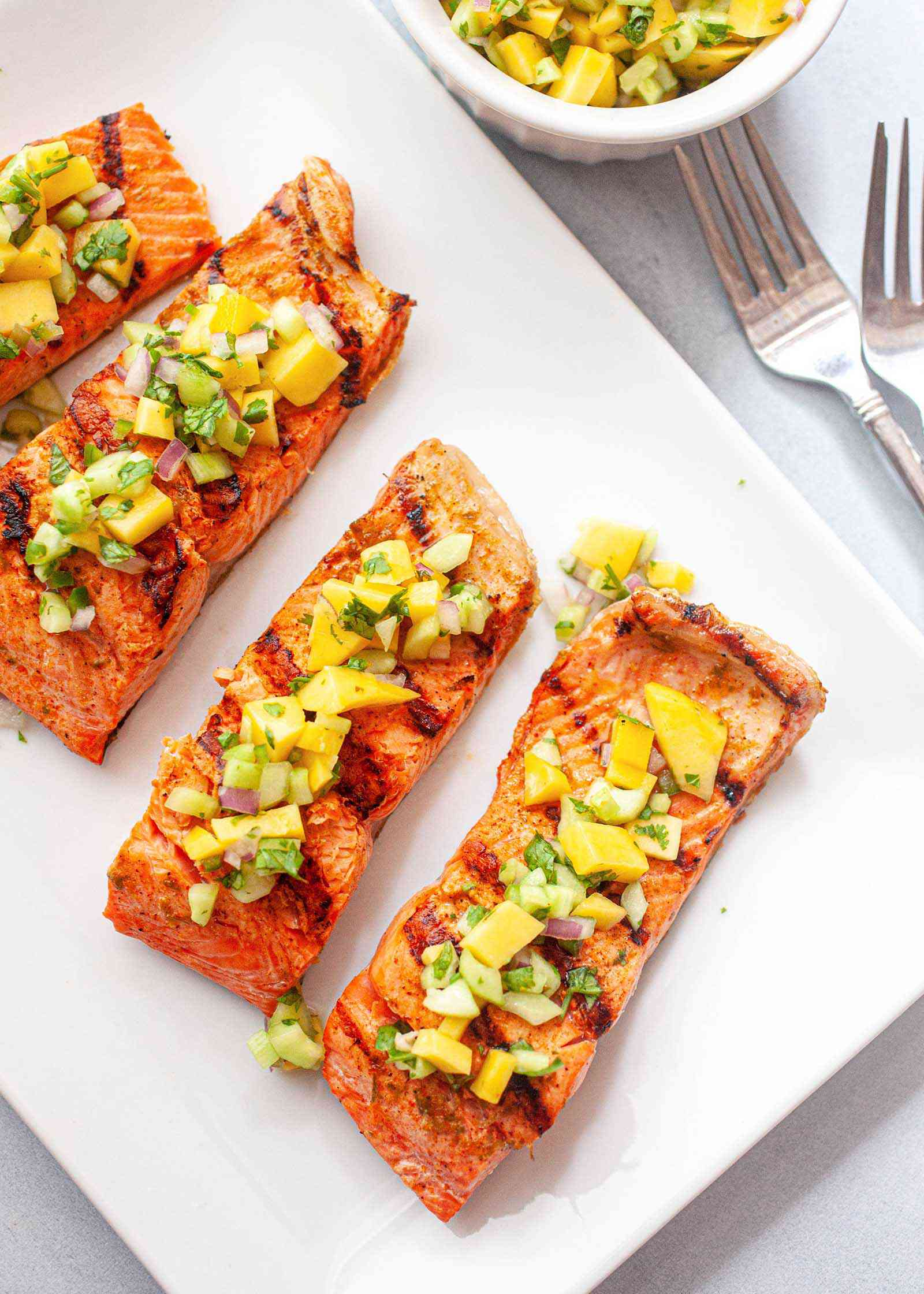 Grilled Salmon with Cucumber Salsa - grilled salmon portions on a plate with fresh salsa