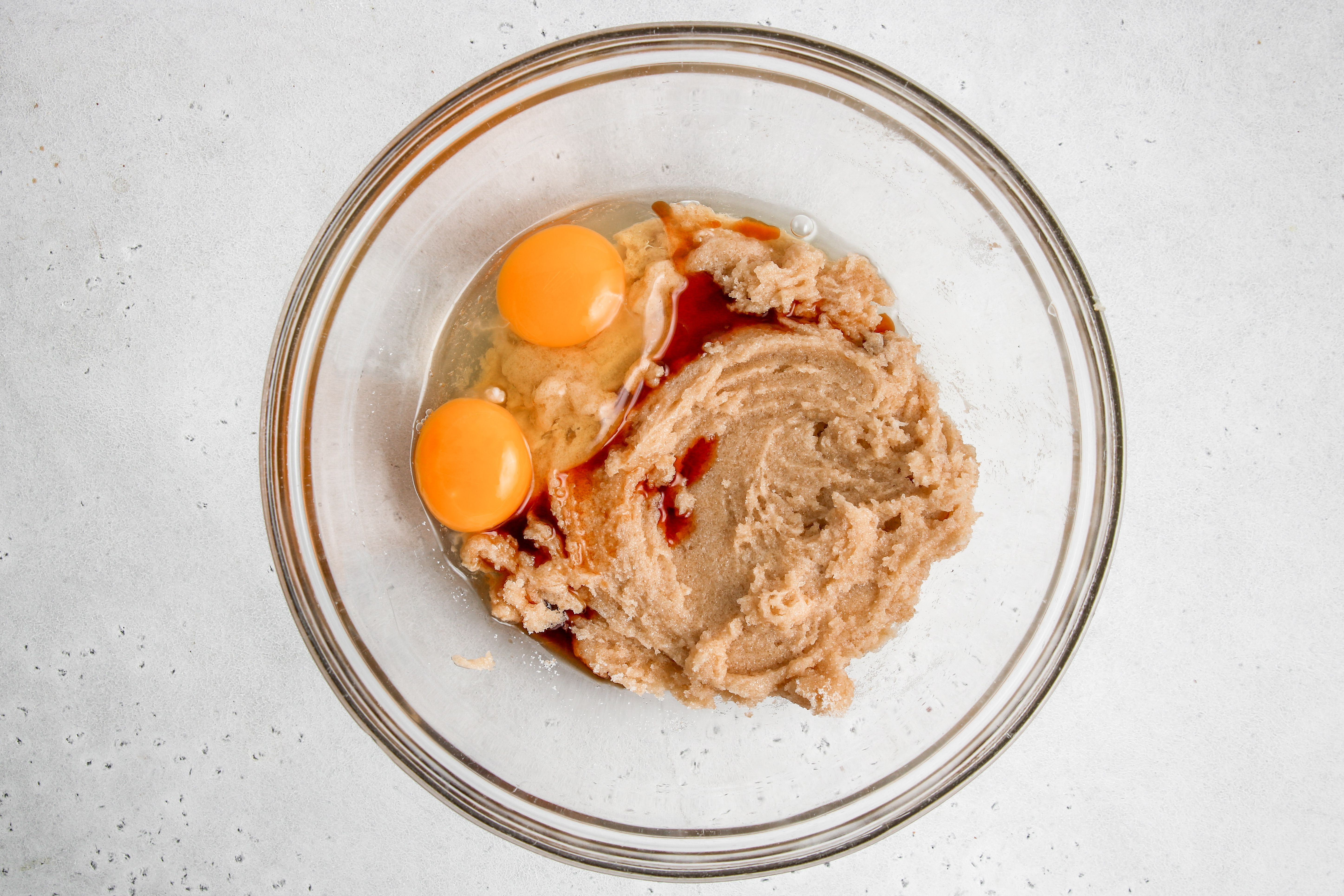 Eggs and vanilla added to creamed butter and sugar for easy chocolate chocolate cookies.