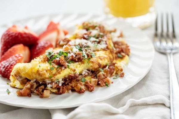 Horizontal image of the best corned beef omelet. The folded omelet is covered in browned corned beef. Grated cheese and parsley are on the top of the omelet. A white cotton napkin is partially under the plate. A fork rests on the napkin which is to the right of the plate. A partial view of a glass of orange juice is above the plate. Halved strawberries are to the left of the omelet on the plate.