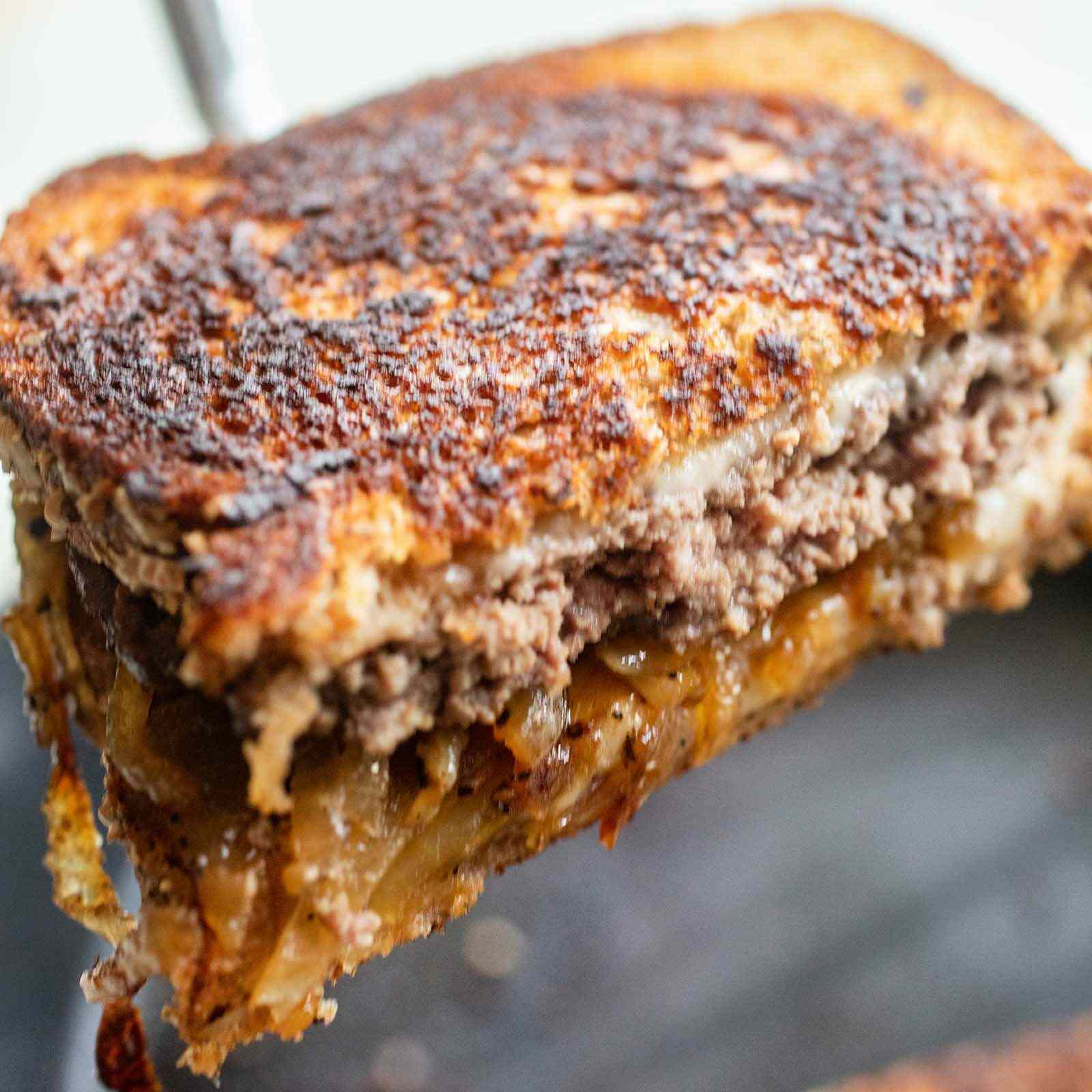 Best patty melt with toasted bread, melted cheese and beef patty being lifted with a spatula.