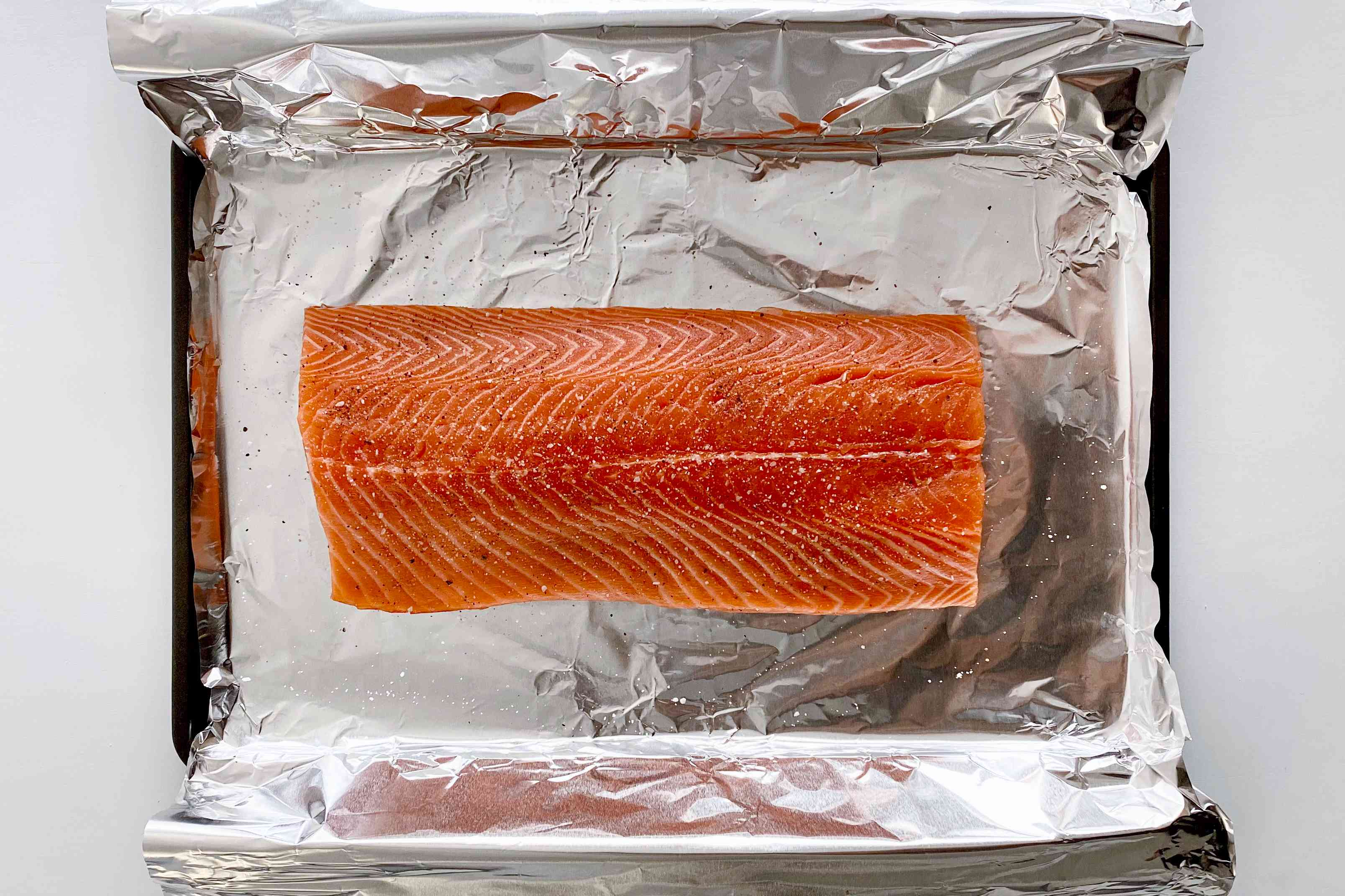 Unbaked salmon on a foil lined baking sheet to make Garlic Butter Baked Salmon.