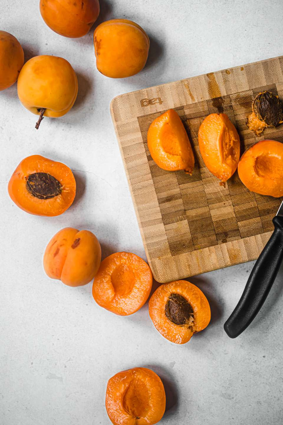 Apricots whole and sliced with a wood cutting board