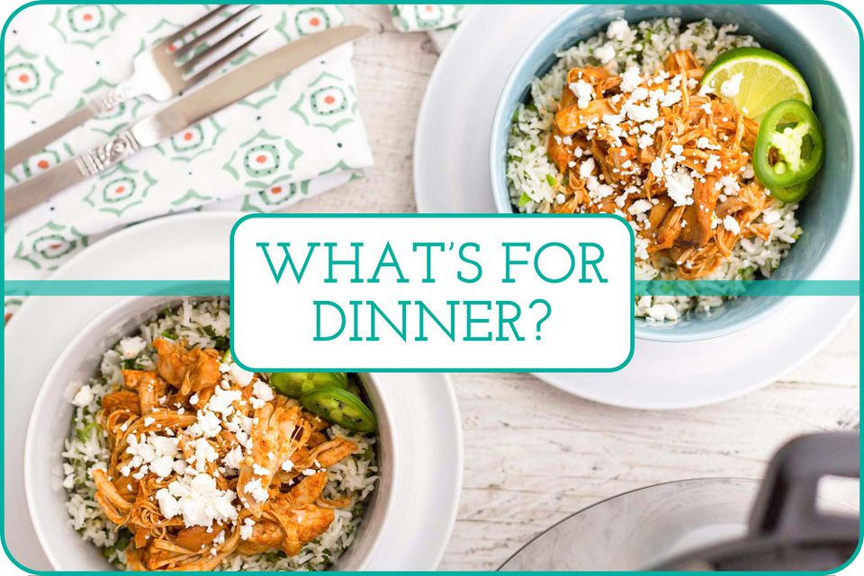 """The words """"What's for Dinner"""" is written across in the middle of the image. Two bowls of pressure cooker chipotle chicken with rice, herbs, sliced jalepano, lime wedge and topped with cojita cheese. The bowls each have a white plate underneath. A partial view of a pressure cooker is in the right lower corner. A fork and knife are resting on a green and red patterned linen in the upper left corner."""