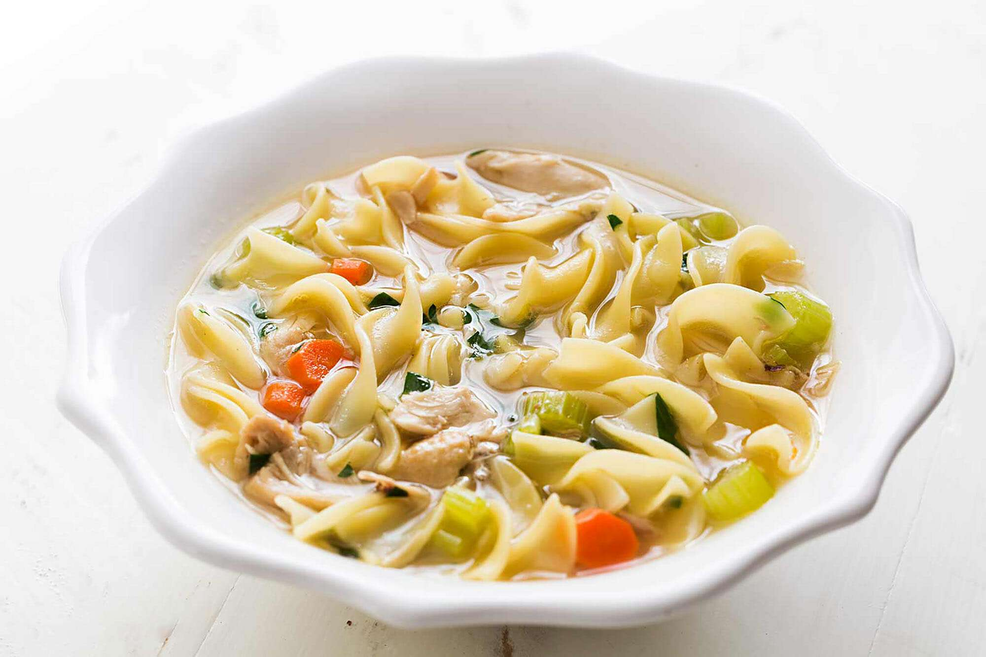 Easy chicken noodle soup in a white bowl.