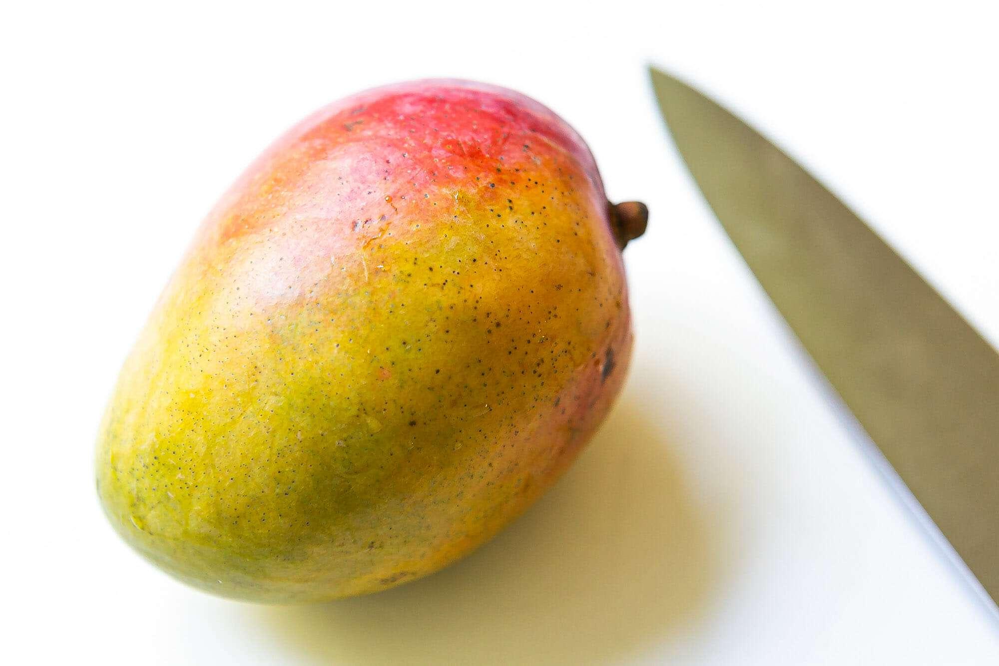 Ripe mango on a cutting board with a knife