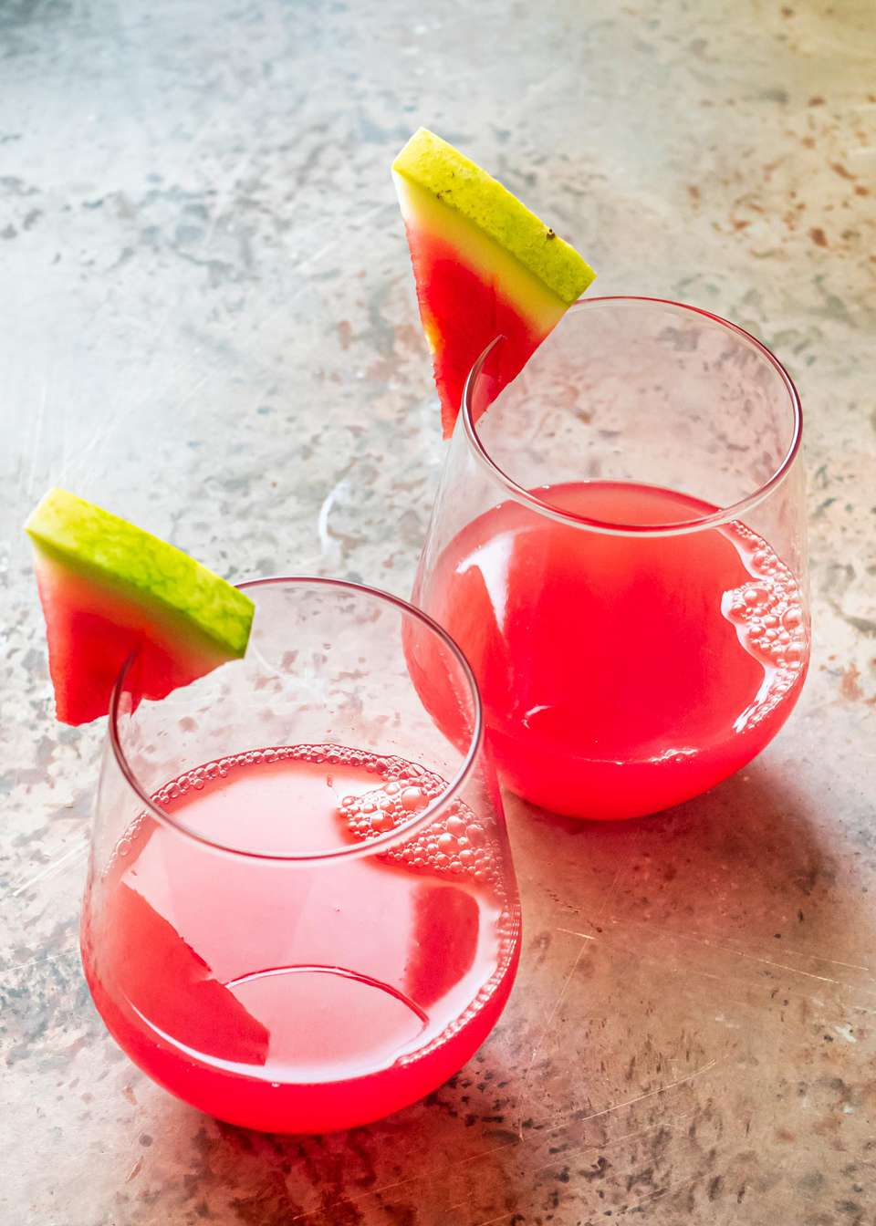 Two wine glasses with watermelon drinks inside and a thin slice of watermelon on the edge.