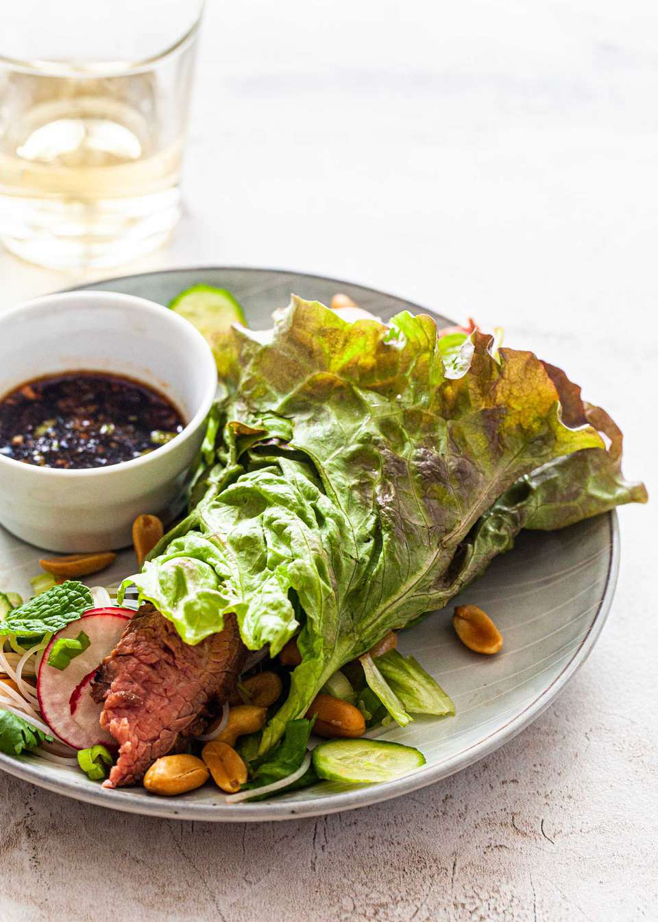 Asian steak lettuce wraps with sliced steak, cucumber, peanuts, radish and a dipping sauce.