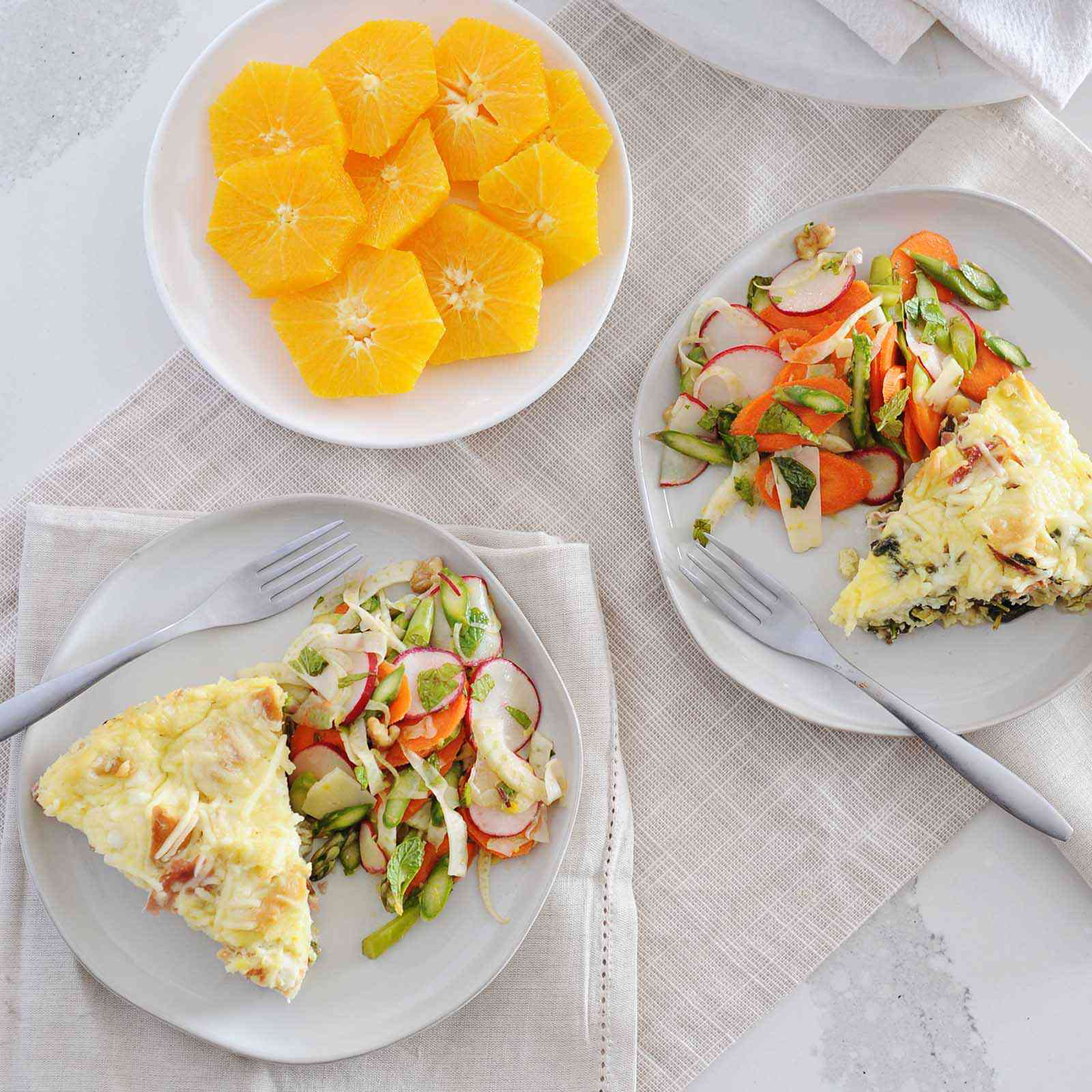 Two plates with a slice of breakfast strata on each as well as a spring salad. Sliced radish and chopped asparagus are visible in the salads. A fork is on each plate as well. Supremed sliced oranges are laid on a white plate set in the middle of the two plates with breakfast casserole inside. Cream linens are under the plates and the rest of the casserole is visible in the upper right corner with a plate and linen underneath.