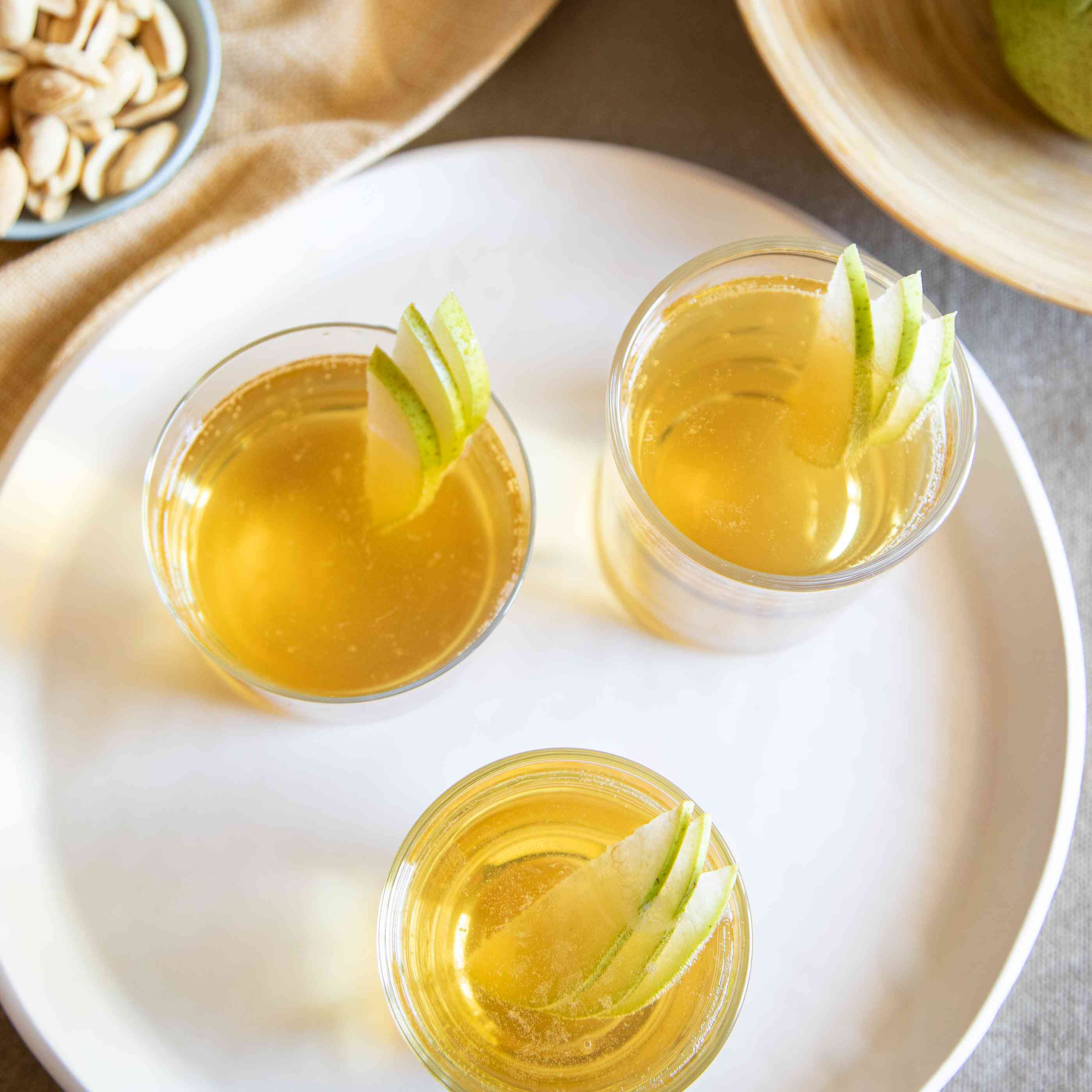 Overhead view of spiced pear punch in glasses on a tray.