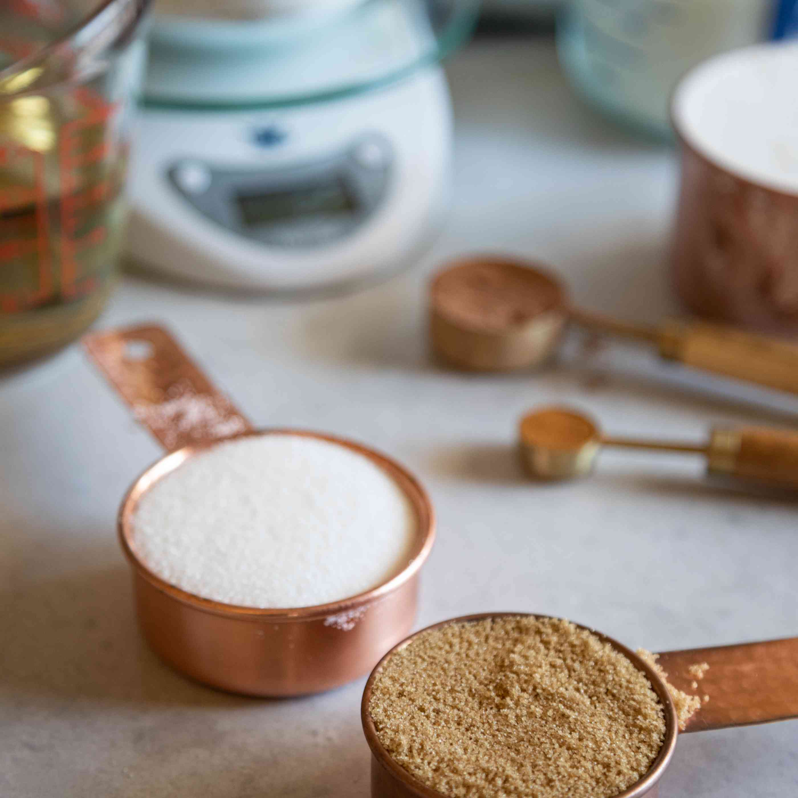 Measuring cups with sugar and measuring spoons, scale and flour in the background to show the best way to measure flour.