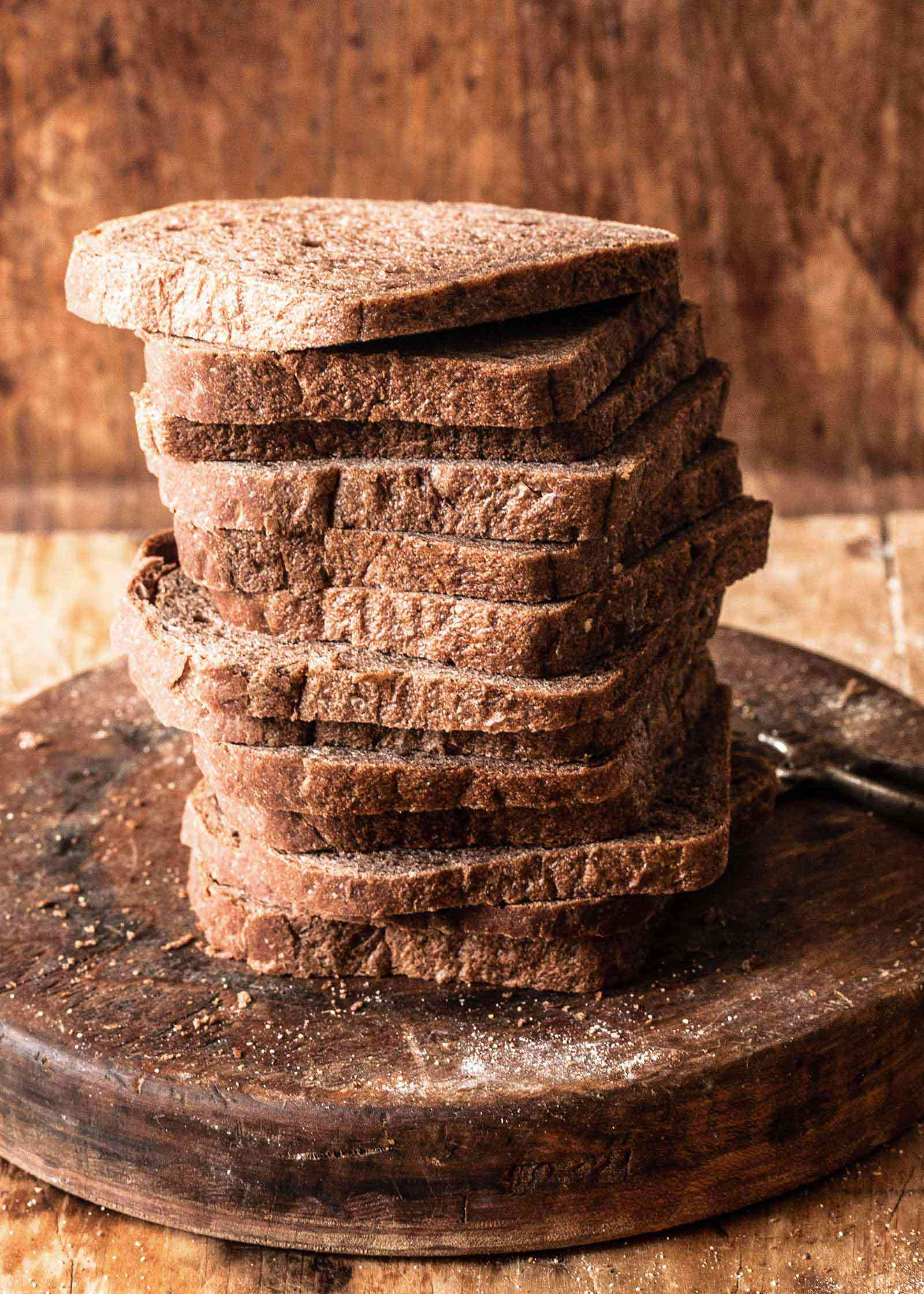 A stack of slicked homemade rye bread slices on a board