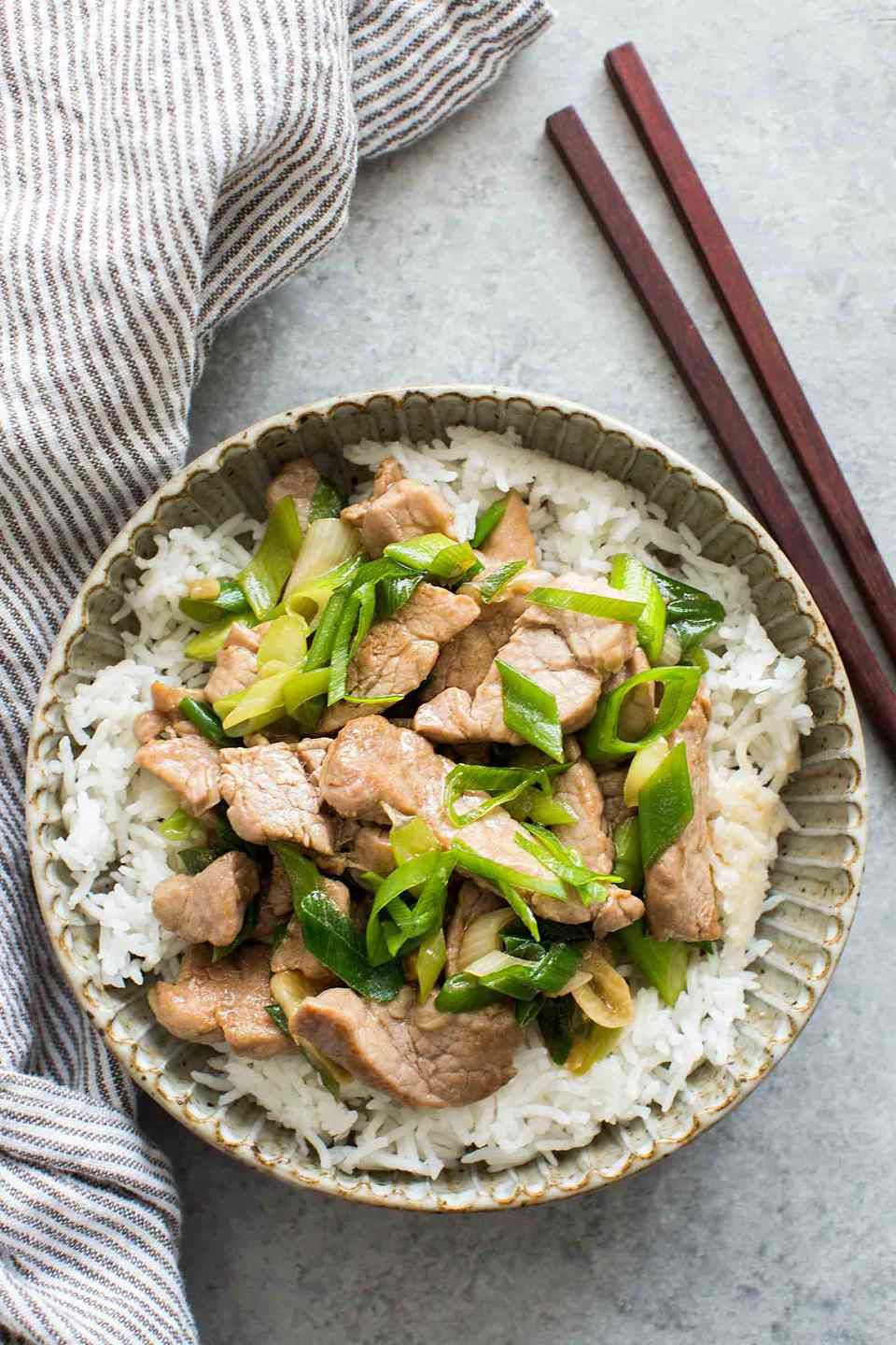 Pork Stir Fry with Green Onion in a bowl with chopsticks beside
