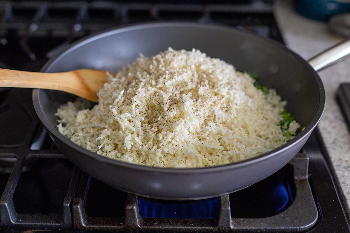 Cauliflower rice is heaped in a non-stick skillet on a gas stove. A wooden spatula is resting inside.