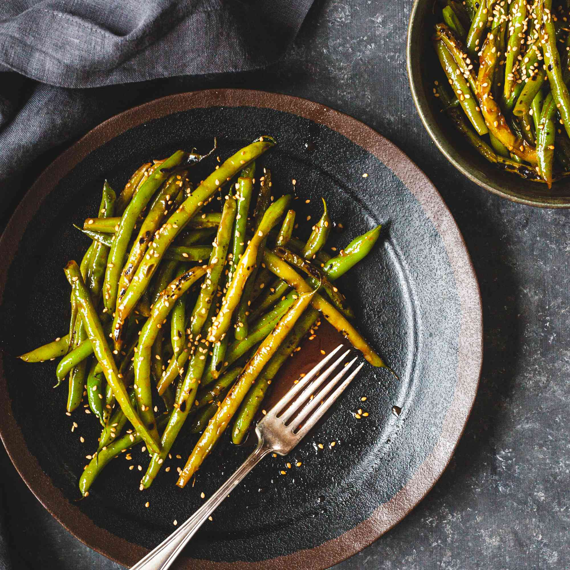 Spicy Blistered Green Beans with Gochujang served on two plates.