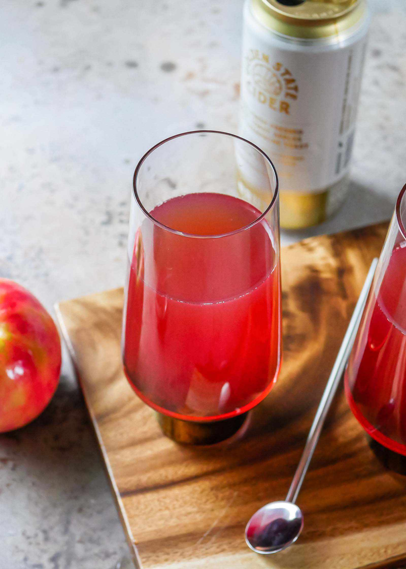 An overhead shot of a Hard Cider and Pomegranate Mimosa with a stir stick, apple, second mimosa and can of cider surrounding the beverage.