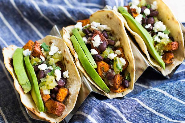 a row of Sweet Potato Black Bean Tacos topped with avocado, cotija cheese, and salsa verde