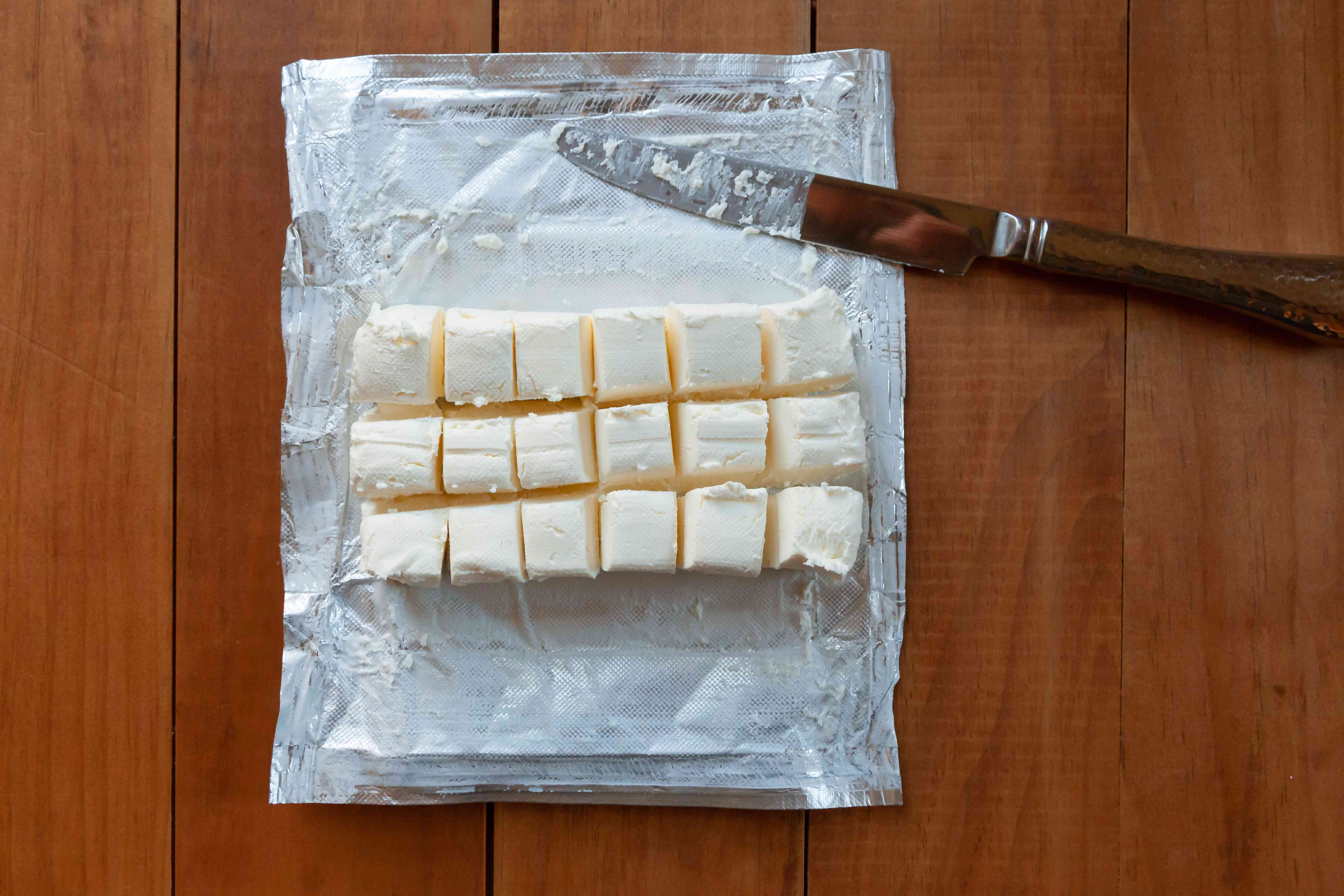 A block of cream cheese cut into squares to make a whipped cream frosting recipe.