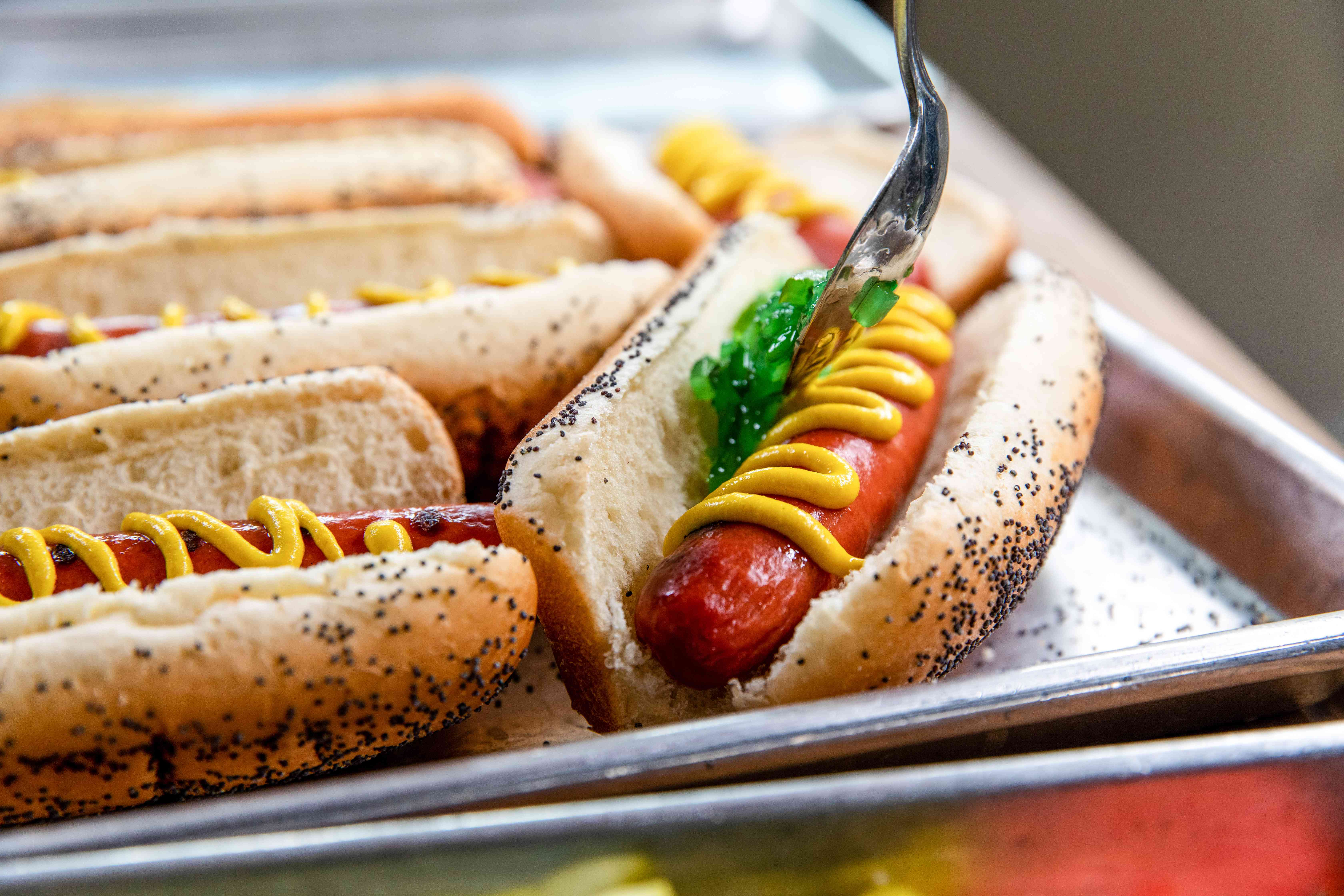 Topping a Chicago hot dog with mustard and sweet pickle relish.