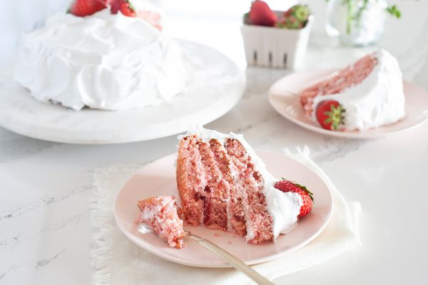 A slice of Strawberry Layer Cake Made with Fresh Strawberries on a plate with a fork.