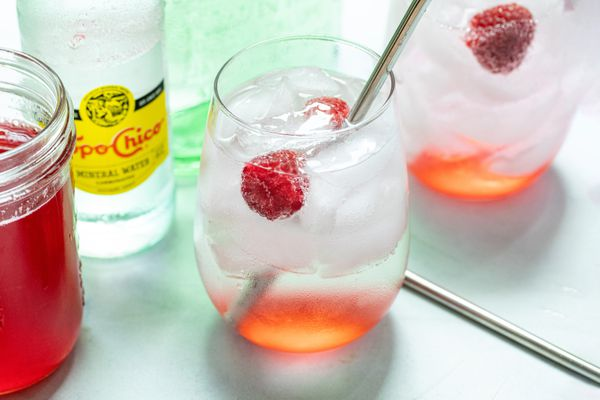 Raspberry Ranch water in two glasses and garnished with raspberries.