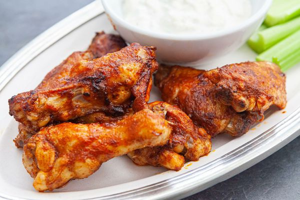 Close up of buffalo wings recipe with blue cheese dressing and celery.