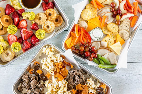 Three baking trays for kids lunch ideas. Each tray has a different type of food on it. The lower tray has popcorn, chips and chocolate covered oranges on it. The tray on the right has vegetables, cheese, crackers and fruit with a dip. The tray on the left has mini pancakes, strawberries and egg bites with maple syrup.