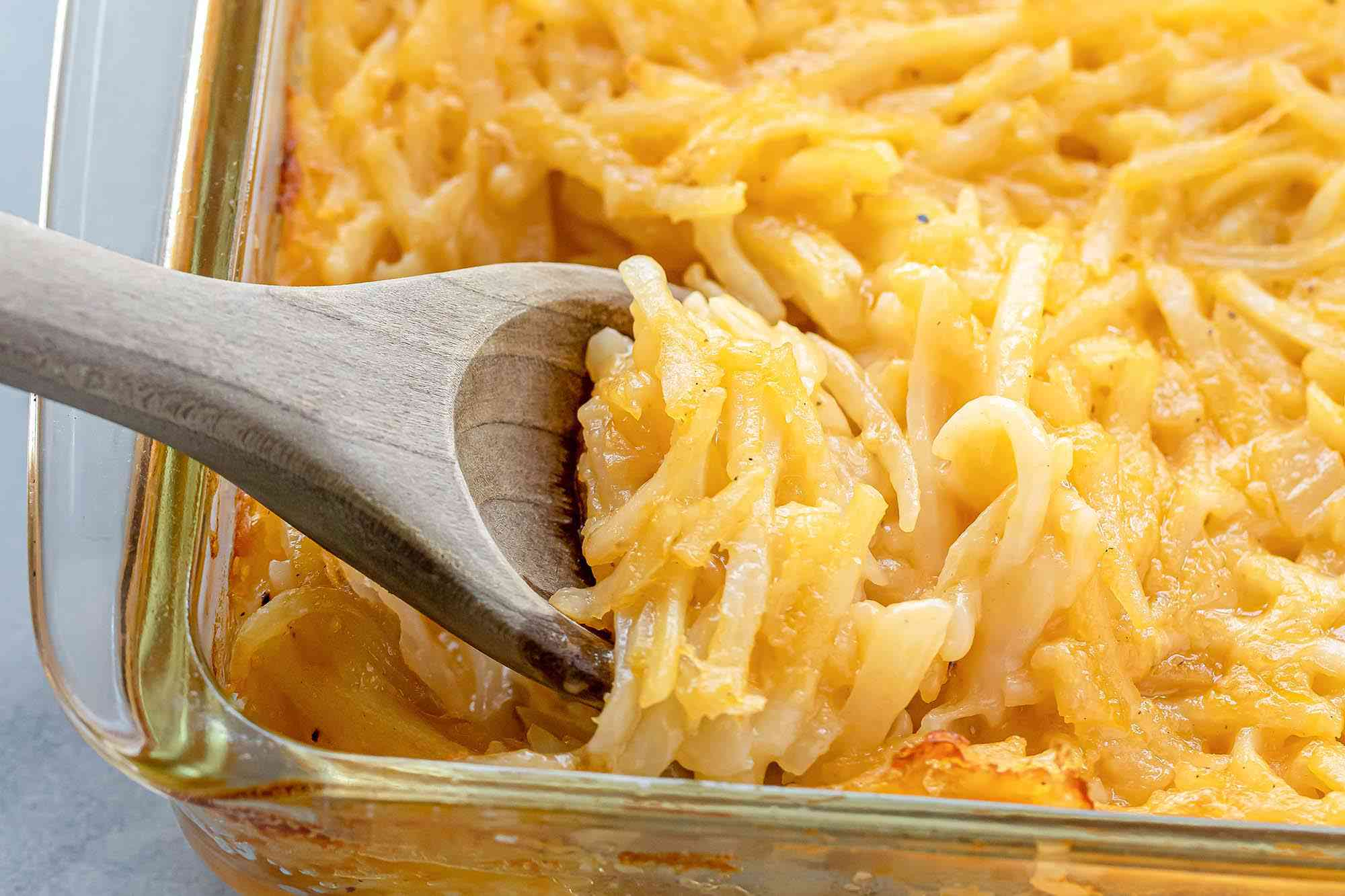 A close up side view of a glass casserole dish with a wooden spoon scooping out the potato casserole.