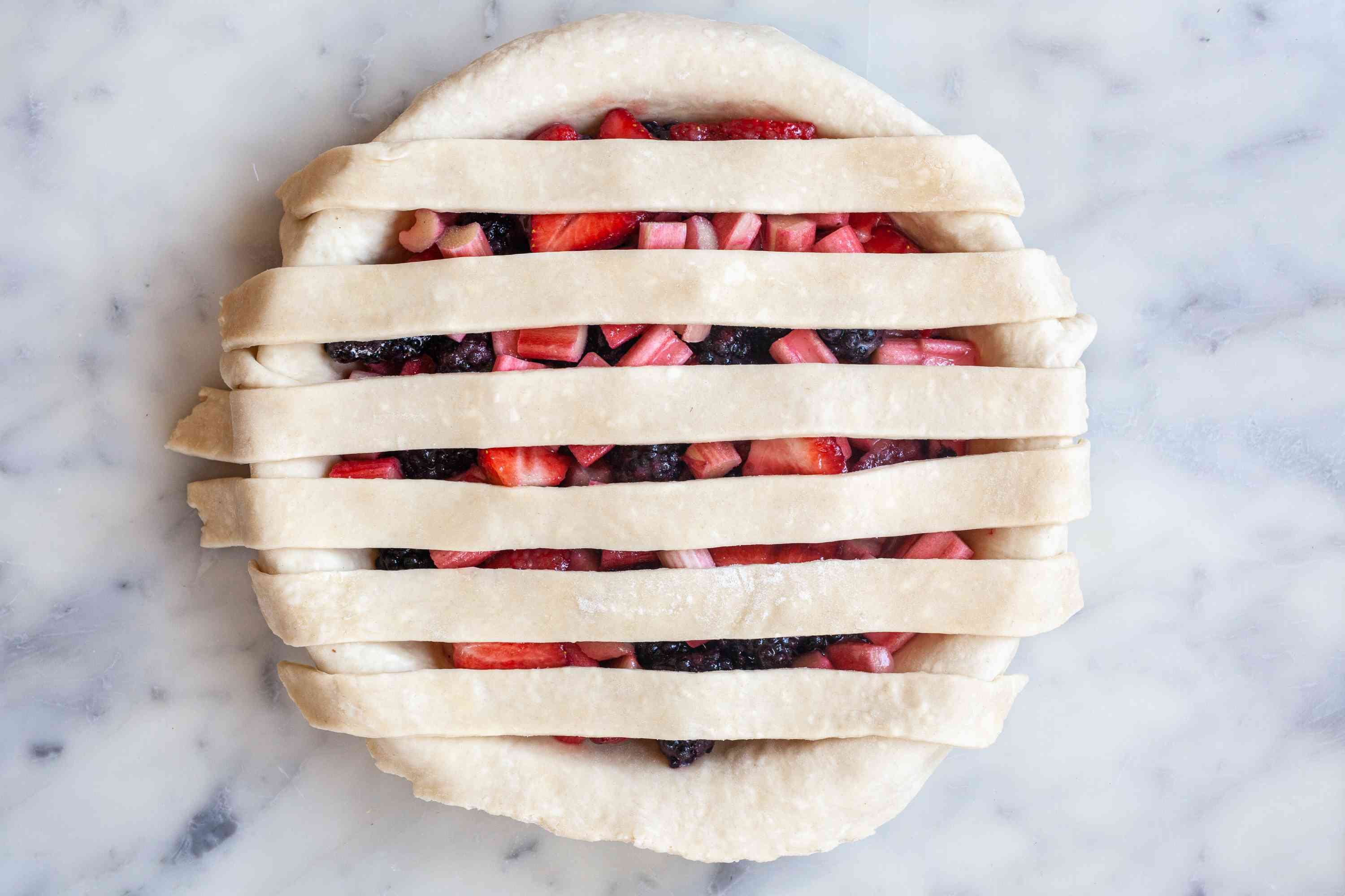 Laying strips over filling to show how to make a lattice crust.