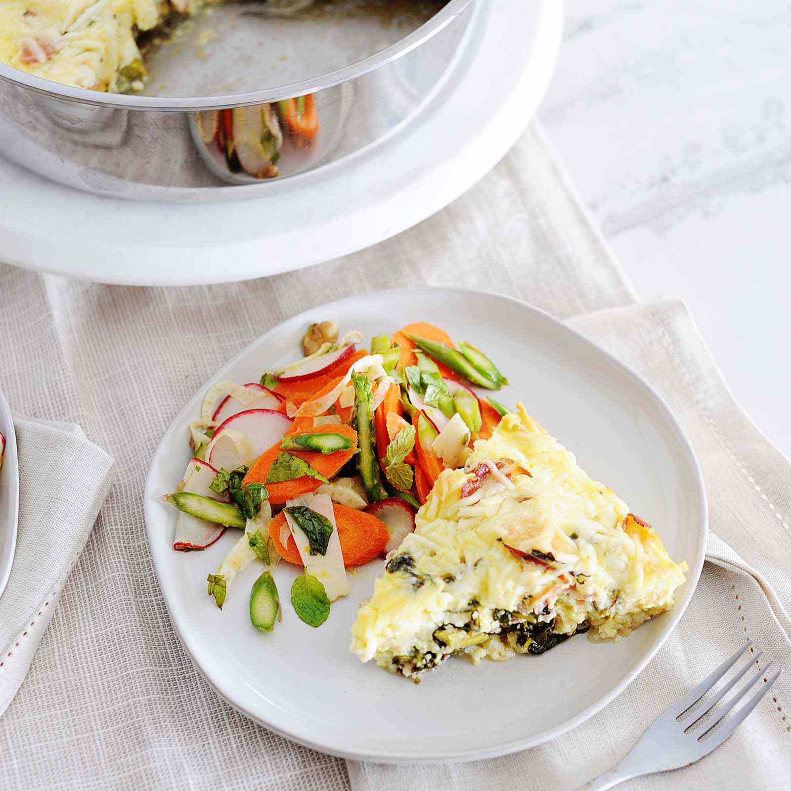 A white plate with a side view of healthy breakfast casserole and a chopped spring salad of asparagus, carrots and radishes. Above the plate is the skillet with the breakfast casserole inside. Two slices are missing from the casserole. Cream linens are under the plate and the skillet is on a round tray.
