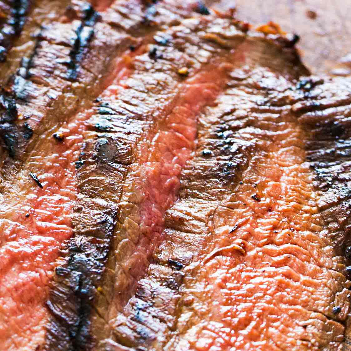 Grilled Flank Steak with brown edge and pink center sliced thinly