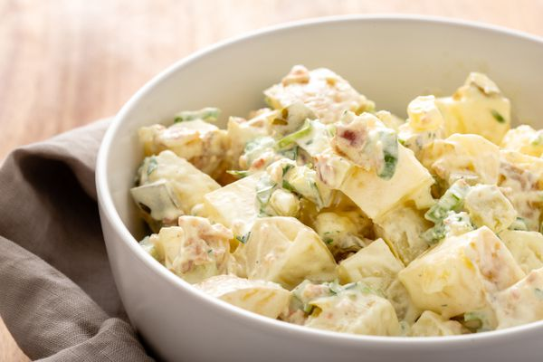 Side view of homemade potato salad in a white bowl.