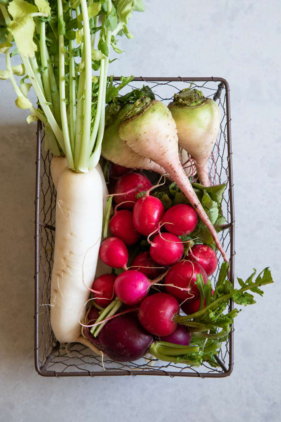 All types of radishes in a metal basket