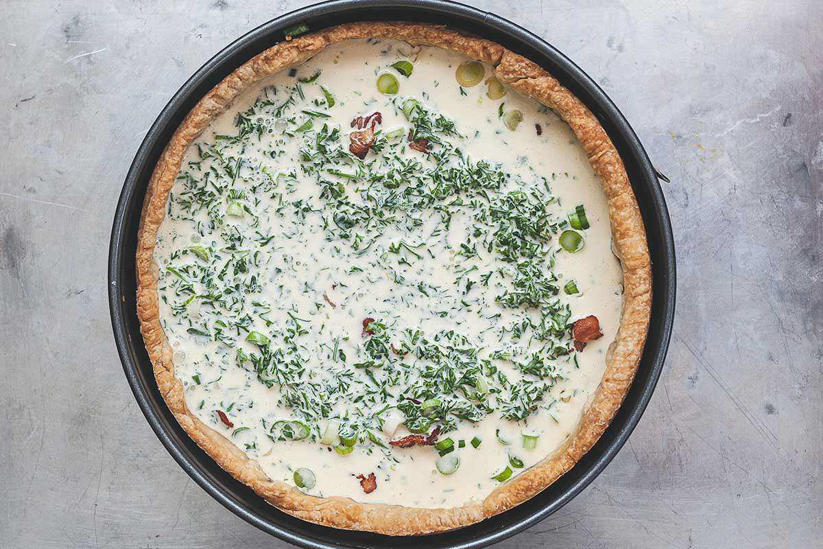 A homemade deep-dish bacon and cheddar quiche is on a countertop with an unbaked filling. The crust is golden brown and in a springform pan. Creamy filling with bacon, parsley and sliced scallionsns are visible in the crust.