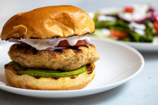 Side view of a herbed chicken burger with lemon mayo