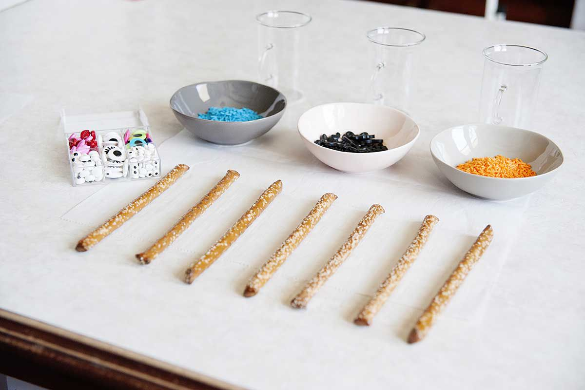 Pretzel sticks, decorations, and sprinkls lined up on a counter.