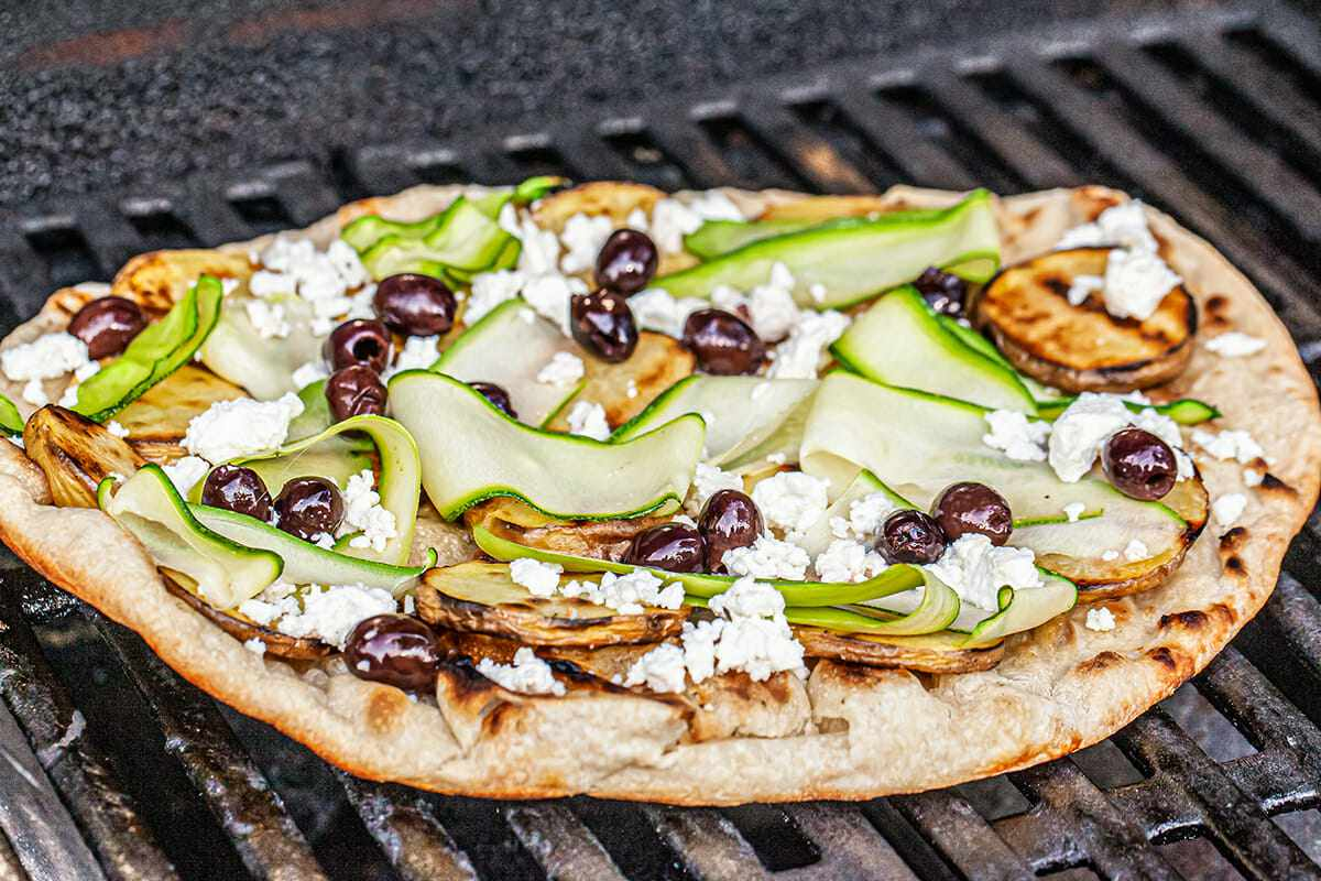 Pizza dough on a grill topped with strips of zucchini, olives and cheese to make a healthy grilled pizza..