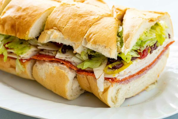 Side view of an italian sandwich on a platter that is cut into slices. Meat, cheese and toppings are layered on the sandwich.