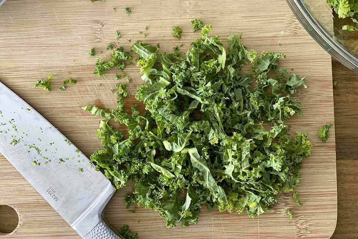 Kale being chopped on a cutting board for a Fall Vegetable Salad with Bacon and Maple Dijon Vinaigrette.