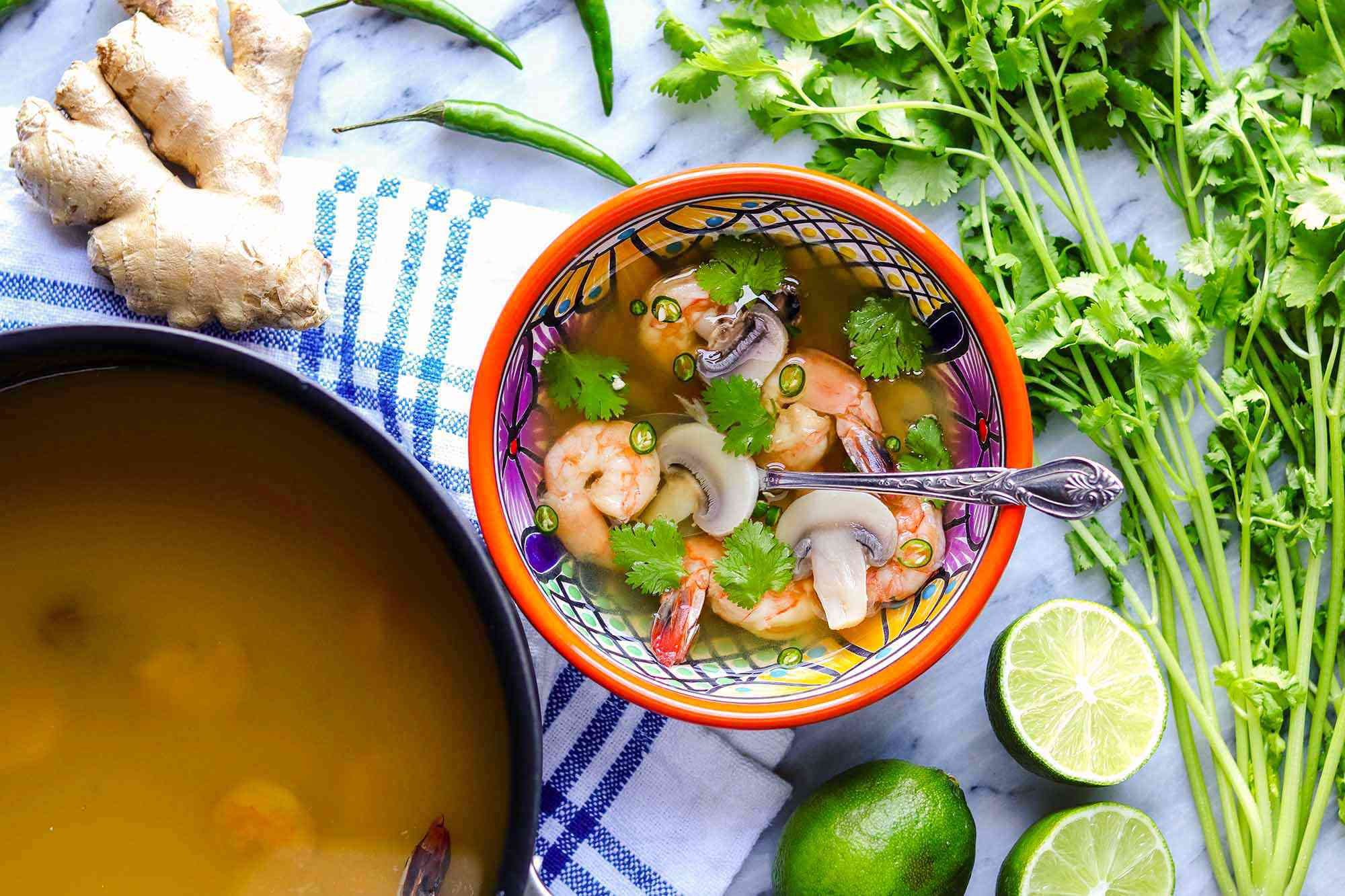 Thai soup with shrimp is in a brightly colored bowl with a silver spoon. A bunch of cilantro and halved limes are to the right of the bowl. To the left is a black pot of soup as well as a blue striped linen and a knob of ginger.