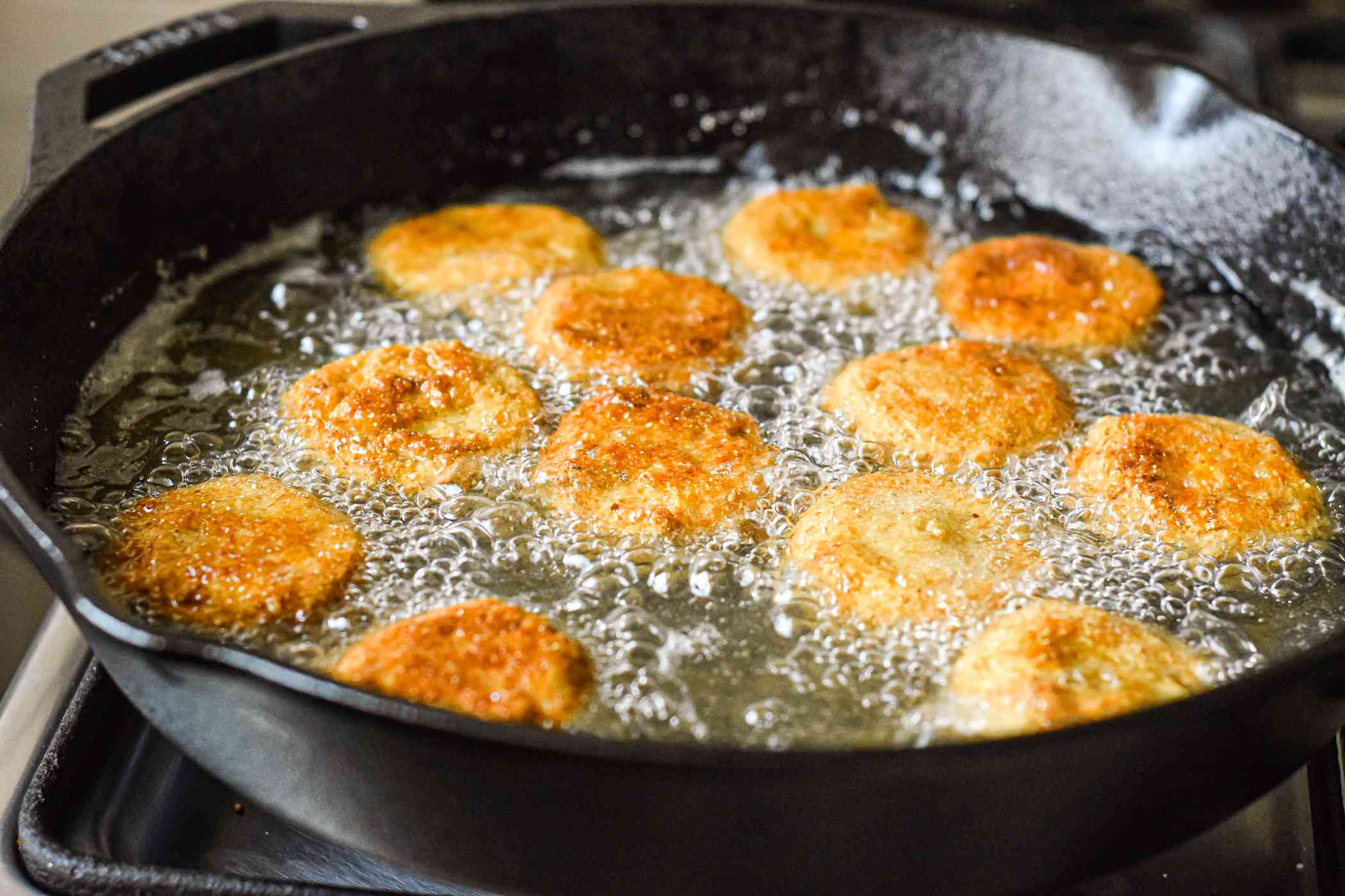 Frying green tomatoes in a cast iron skillet.