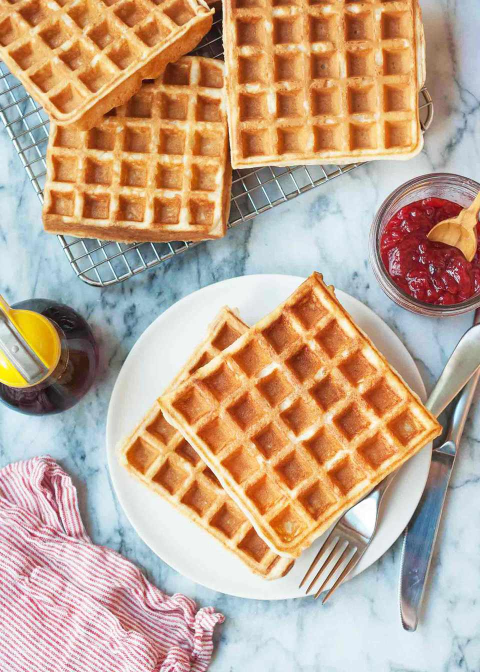 Buttermilk waffle recipe on a round plate with extra waffles on a cooling rack nearby