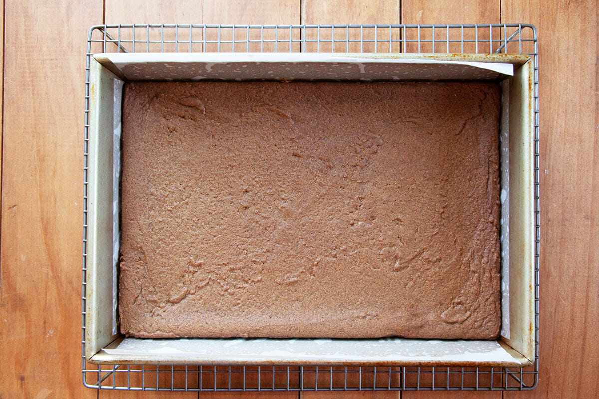 Unfrosted Gingerbread Bars in a lined baking pan and cooling on a cooling rack.