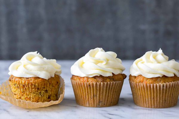 Three Carrot Cake Cupcakes topped with cream cheese frosting, one of them is partially unwrapped