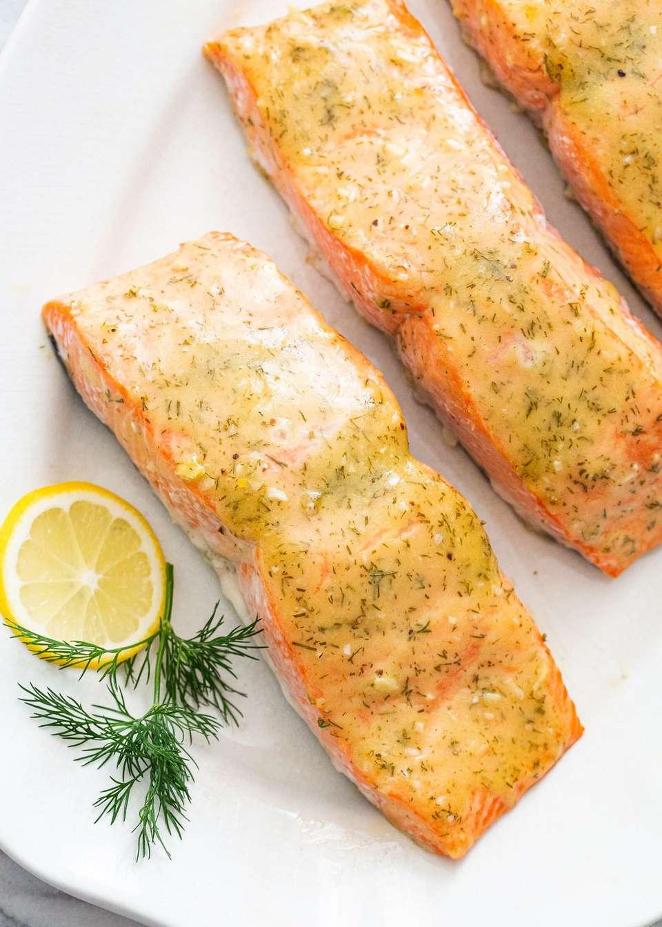 Baked honey mustard salmon on a platter with lemon garnish.