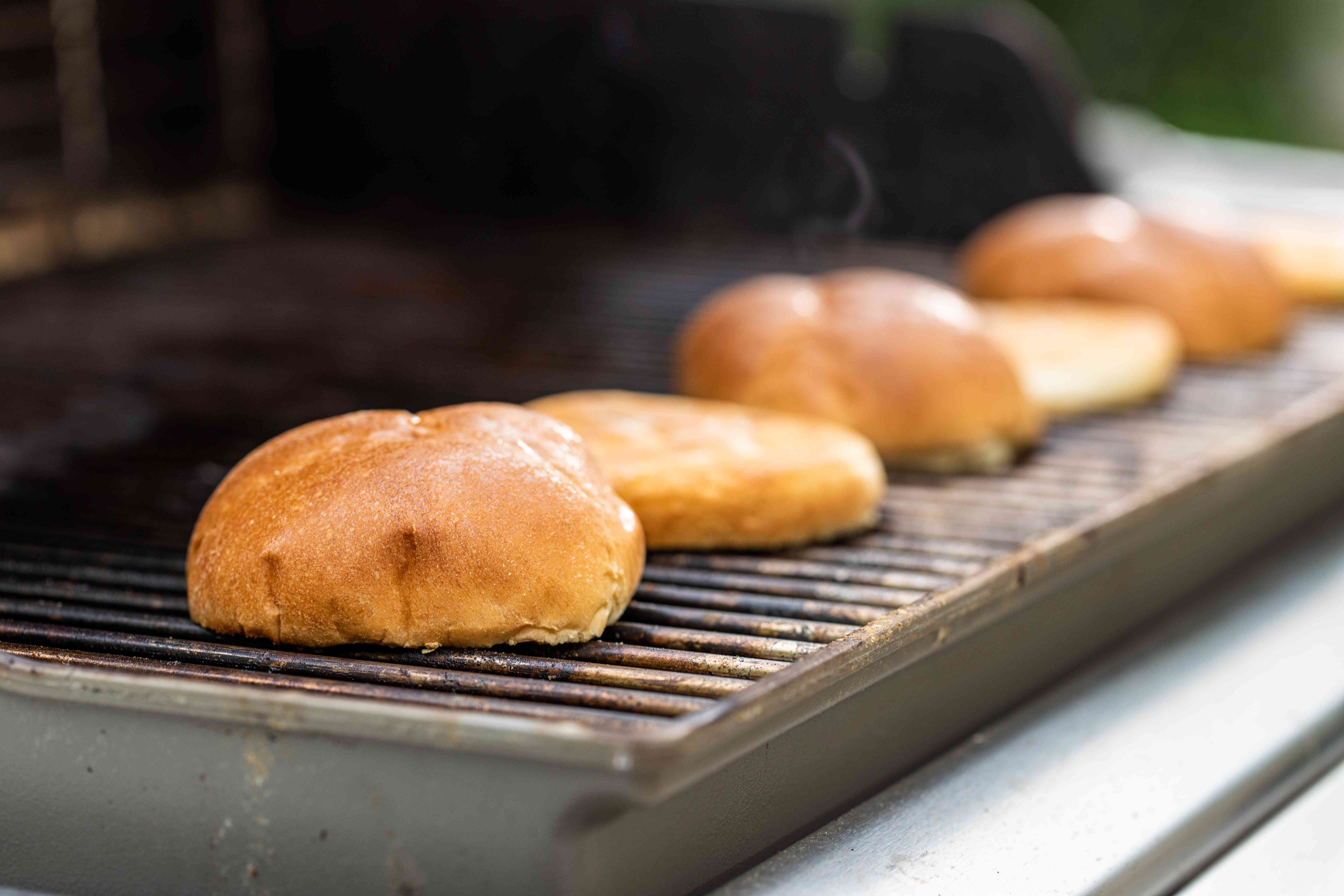 Toasting buns on a grill for the best bacon cheeseburger