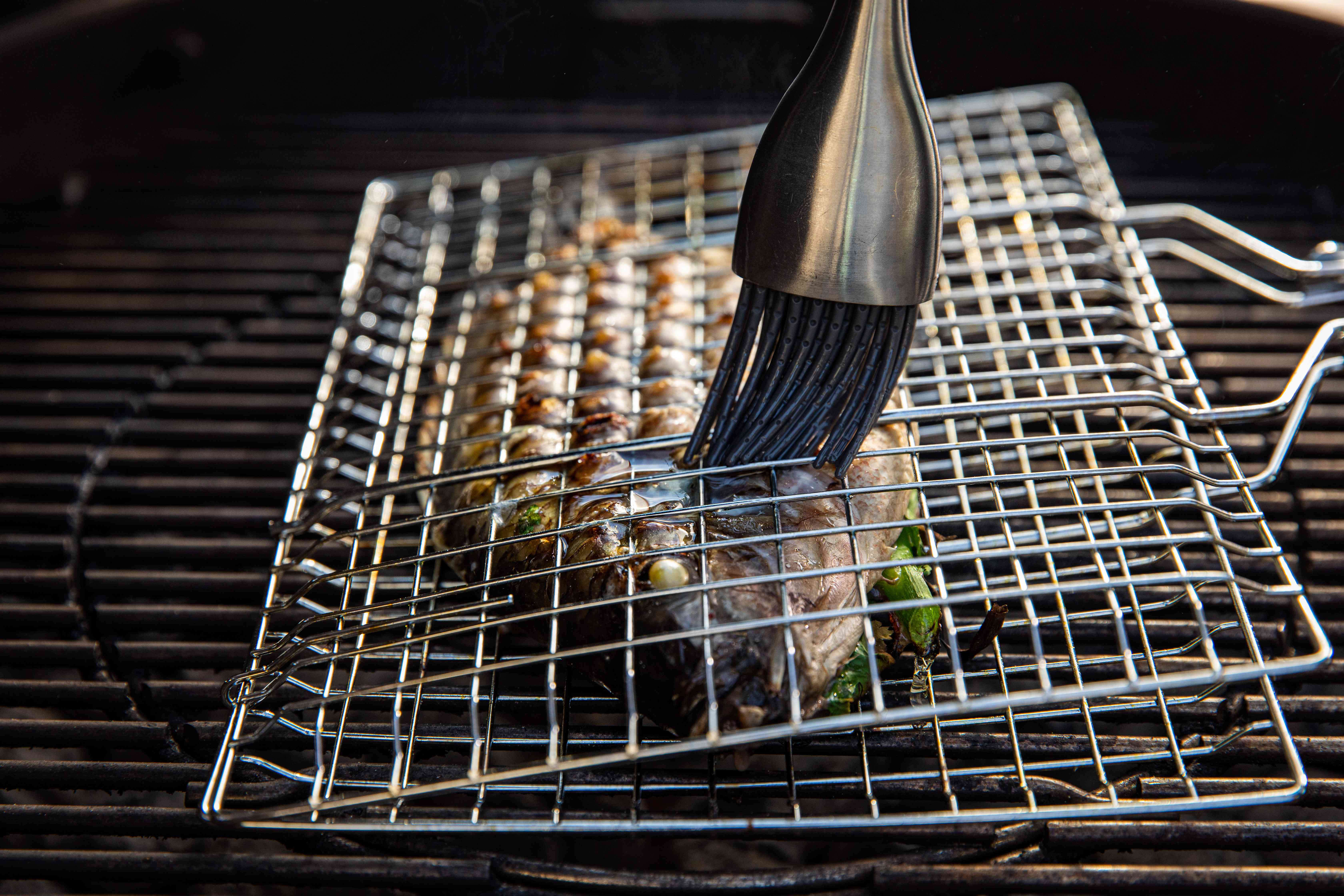 Grilled whole fish stuffed with herbs and chilies in a grill cage and brushed with oil.